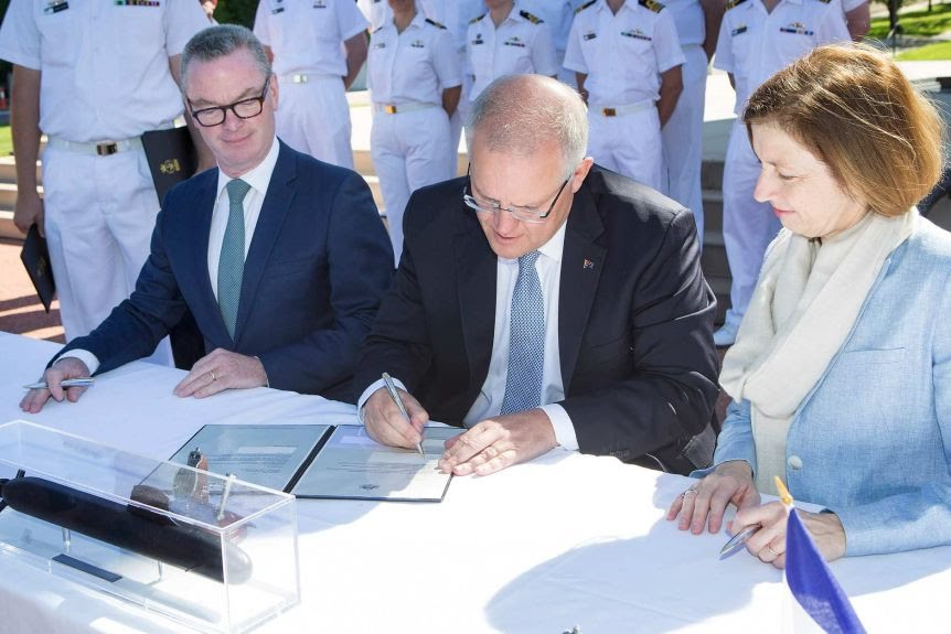 Scott Morrison signs a document with Christopher Pyne and Florence Parly sitting alongside him. Naval officers stand behind them