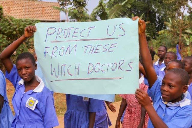 Ugandan children carrying a placard that says 'protect us from these witch doctors'.