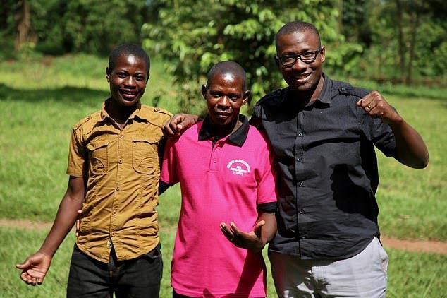 Three men stand side by side embracing all wearing bright t-shirts.