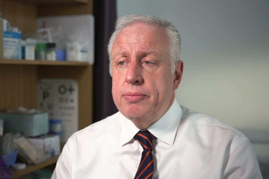 Dr Harry Nespolon, President of the Royal College of General Practitioners looks to the camera with a serious expression.