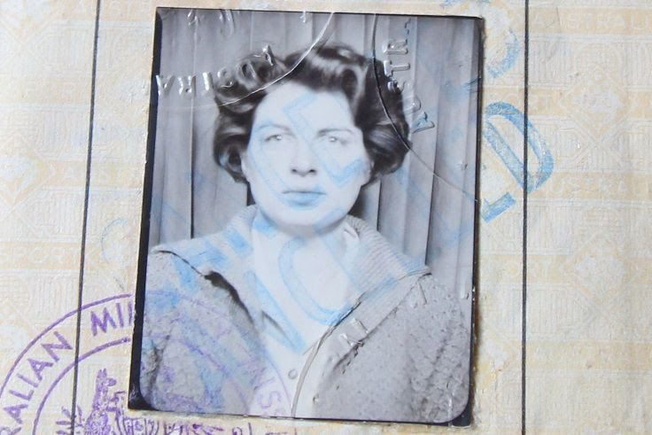 An old black and white passport photo of a woman with dark curly hair.