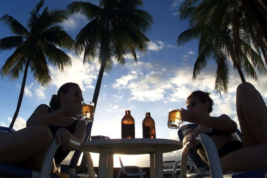 Two women toast with their fears in a tropical paradise under palm trees