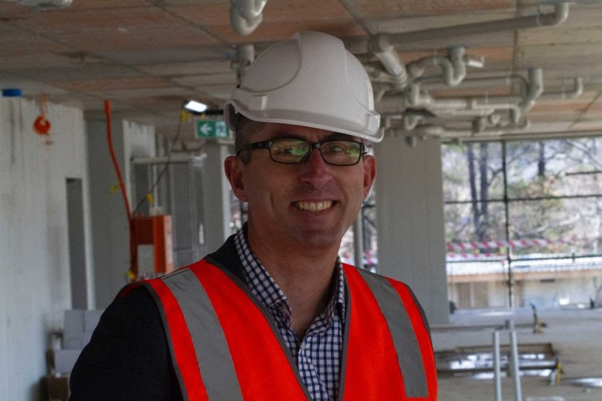 Nicholas Proud, CEO of PowerHousing, in a partially completed home, wearing a high vis orange vest and white hard hat.